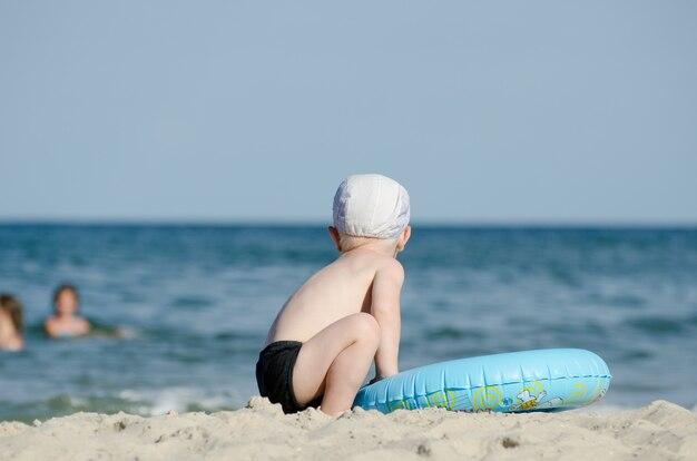 Weinig blonde jongenszitting op de kust met een zwemmende cirkel met zijn rug