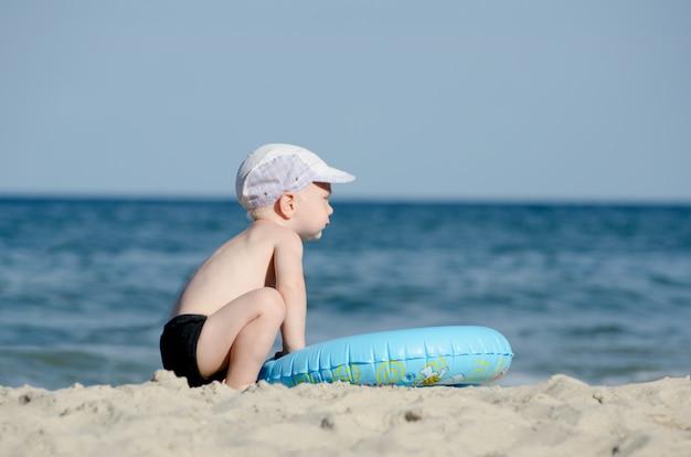 Weinig blonde jongenszitting op de kust met een zwemmende cirkel