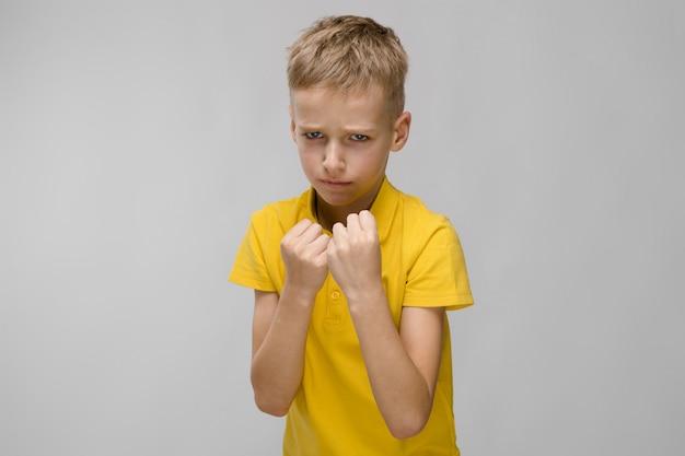 Weinig blonde kaukasische ernstige droevige jongen in het gele t-shirt in dozen doen op grijs