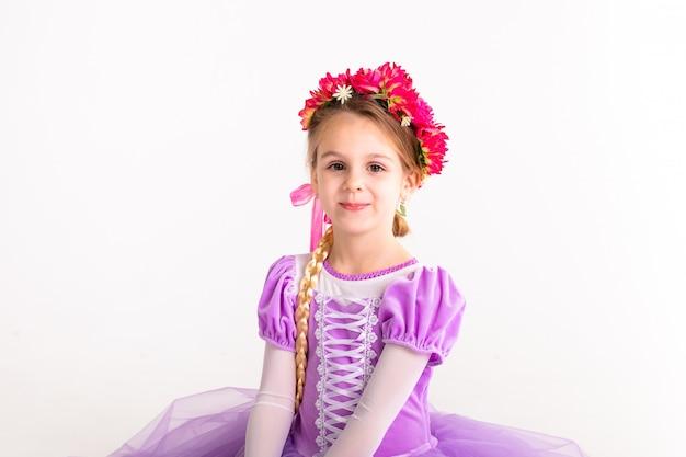 Weinig blondemeisje die de purpere kleding van de feeprinses op witte achtergrond dragen. kinderkostuum voor nieuwjaarsfeest