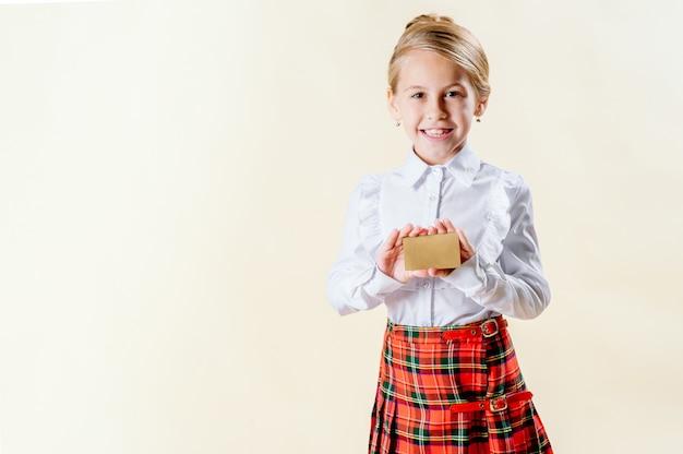 Weinig blondemeisje die een lege kaart in eenvormige school houden