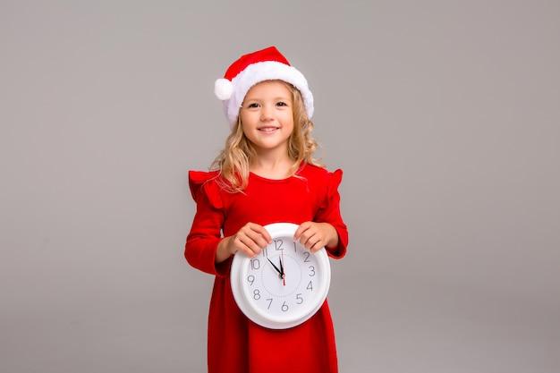 Weinig blondemeisje die in kerstmankostuum glimlachen met witte klok