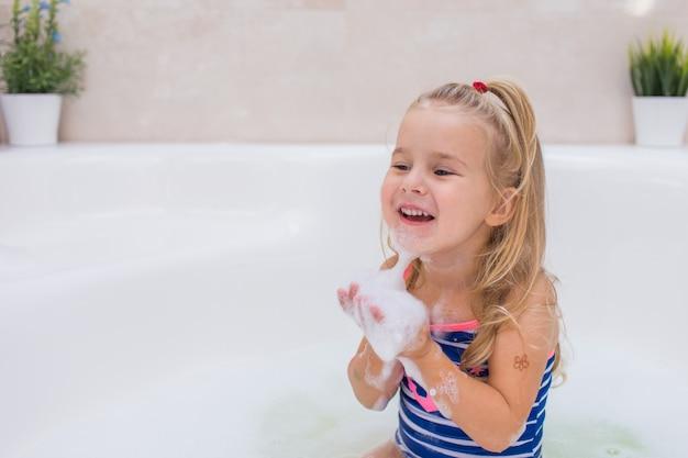Weinig blondemeisje die schuimbad in mooie badkamers nemen. hygiëne van kinderen. shampoo, haarbehandeling en zeep voor kinderen. kinderen baden in groot bad.