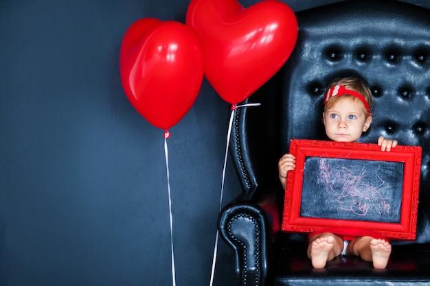 Weinig blondemeisje in rode kleding met rode kroon met harten die op de leunstoel met rode hartballon zitten op de st. valentine dag.
