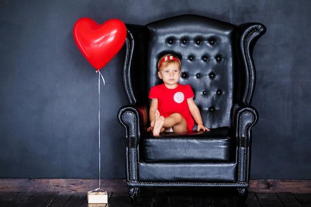 Weinig blondemeisje in rode kleding met rode kroon met harten die op de leunstoel zitten