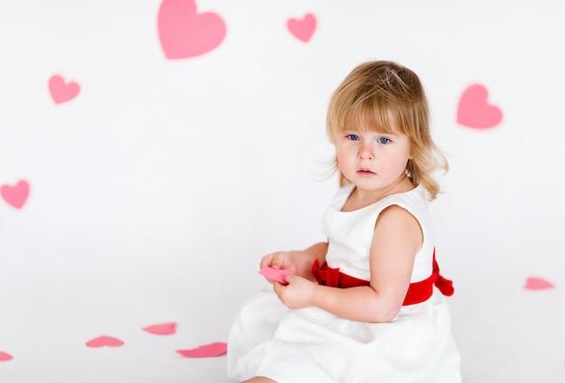 Weinig blondemeisje in witte kleding met rood lint op witte vloer met roze harten op de valentijnskaartendag