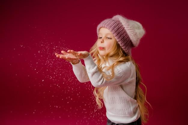 Weinig blondemeisje met gebreide hoed en sweater speelt met de sneeuw