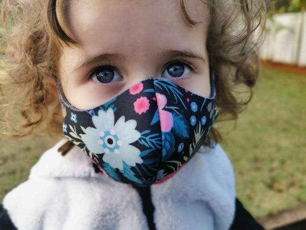 Weinig braziliaans meisje dat gebruikend masker in openlucht glimlacht