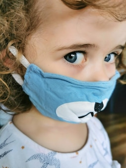 Weinig braziliaans meisje dat masker gebruikt