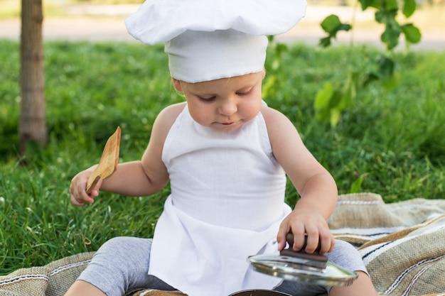 Weinig chef-kok kookt in openlucht lunch op een picknick. leuk kind in een kokkostuum met pan en kokende spatel op de groene aardmuur