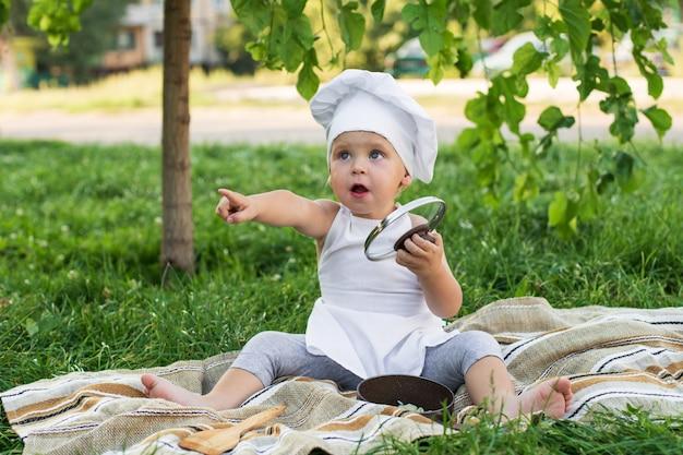 Weinig chef-kok kookt in openlucht lunch op een picknick. leuke jongen in een kokkostuum met pan en kokende spatel op de groene aardmuur