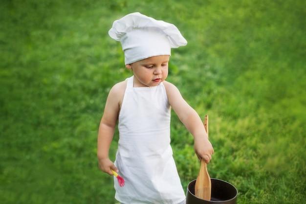 Weinig chef-kok kookt in openlucht op een picknick
