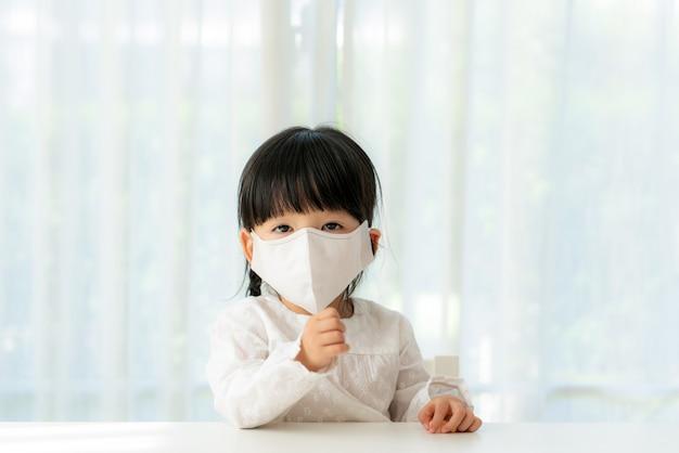 Weinig chinees meisje die gezonde gezichtsmaskerzitting thuis dragen in woonkamer om pm2.5-stof, smog, luchtvervuiling en covid-19 te verhinderen.