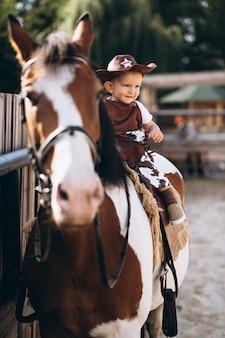Weinig cowboy zittend op een paard