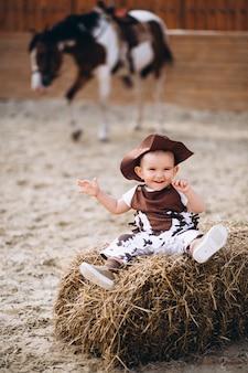 Weinig cowboy zittend op hooi