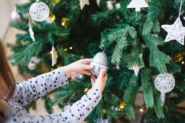 Weinig de holdingsdecoratie van het meisje voor kerstboom, kerstmisbinnenland, die kerstmis en nieuw jaar, huisdecoratie voorbereidingen treffen