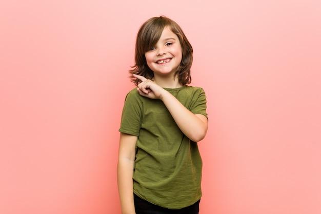 Weinig en jongen die opzij glimlacht richt, die iets toont op lege ruimte.