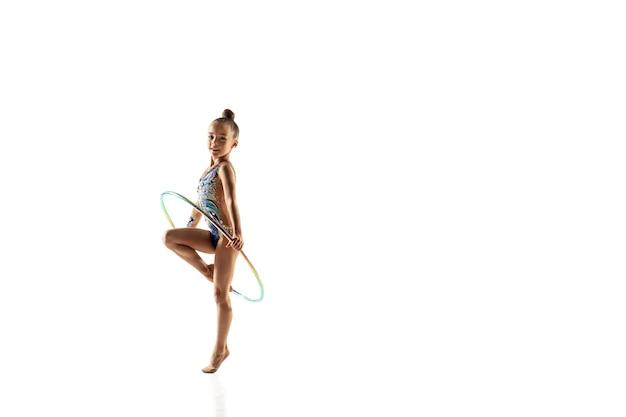 Weinig flexibel meisje dat op wit wordt geïsoleerd. weinig vrouwelijk model als ritmische gymnastiekartiest in heldere maillot.