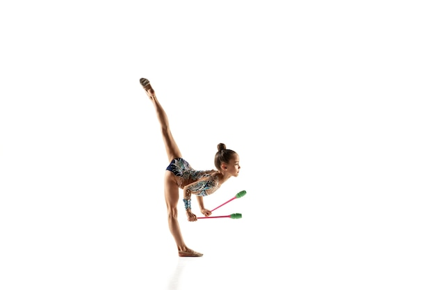 Weinig flexibel meisje dat op witte muur wordt geïsoleerd. weinig vrouwelijk model als ritmische gymnastiekartiest in heldere maillot. gratie in beweging, actie en sport. oefeningen doen met de knotsen.