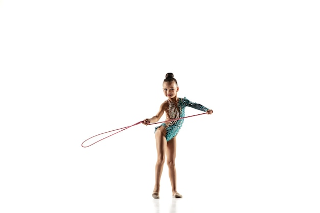 Weinig flexibel meisje dat op witte muur wordt geïsoleerd. weinig vrouwelijk model als ritmische gymnastiekartiest in heldere maillot. gratie in beweging, actie en sport. oefeningen doen met het springtouw.