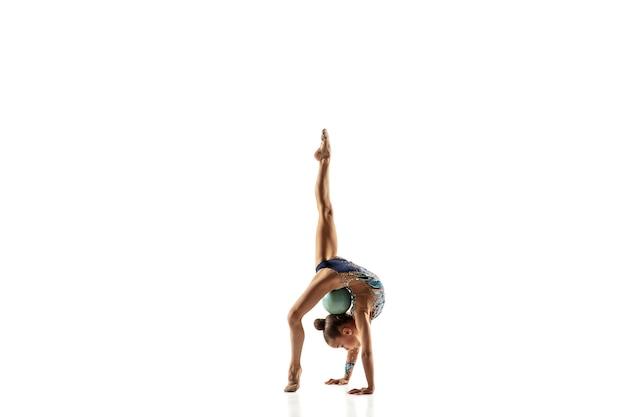 Weinig flexibel meisje dat op witte muur wordt geïsoleerd. weinig vrouwelijk model als ritmische gymnastiekkunstenaar in heldere maillot. gratie in beweging, actie en sport. oefeningen doen met de bal.