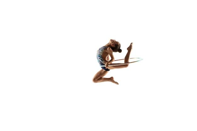 Weinig flexibele vrouwelijke turnster die op witte muur wordt geïsoleerd
