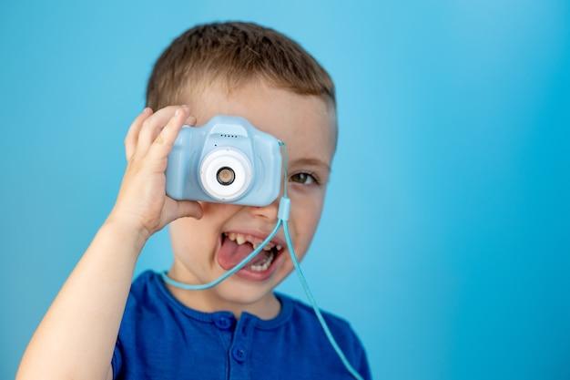 Weinig fotograaf met speelgoedcamera op blauwe achtergrond.