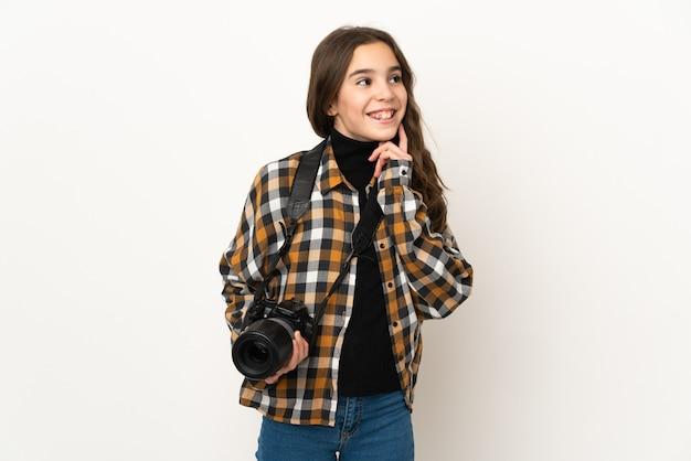 Weinig fotograafmeisje dat op achtergrond wordt geïsoleerd die een idee denkt terwijl het opzoeken