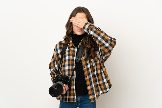 Weinig fotograafmeisje dat op muur wordt geïsoleerd die ogen behandelt door handen. ik wil niets zien