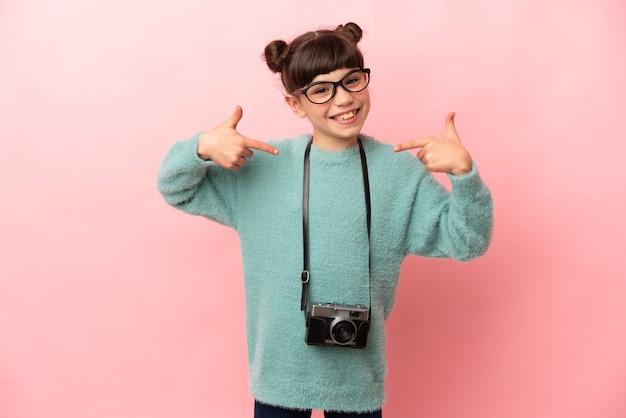Weinig fotograafmeisje dat op roze achtergrond wordt geïsoleerd die een duim omhoog gebaar geeft