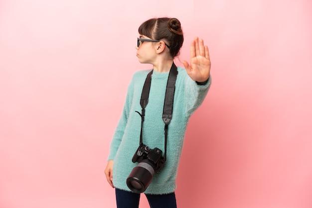 Weinig fotograafmeisje dat op roze achtergrond wordt geïsoleerd die stopgebaar en teleurgesteld maakt