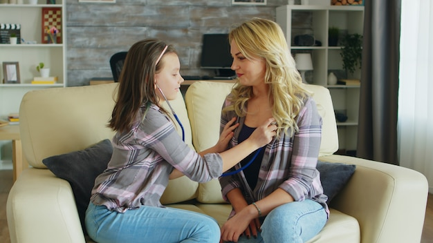 Weinig geleerd van haar moeder om met een stethoscoop naar haar hart te luisteren terwijl ze op de bank zit.