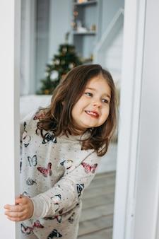 Weinig gelukkig donkerbruin meisje in comfortabele pyjama kijkt van de slaapkamer van het kinderenbed, kerstmistijd