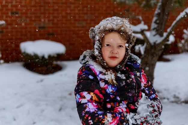 Weinig gelukkig glimlachend meisje in roze werpt snowin de lucht met snawflakes het vliegen