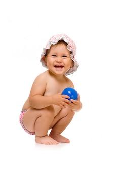 Weinig gelukkig kind in sunhat met bal, dat over wit wordt geïsoleerd