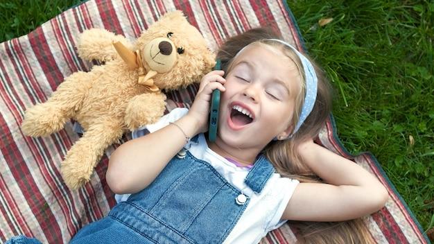 Weinig gelukkig kindmeisje dat op groen gazon met haar teddybeer oplegt die op mobiele telefoon spreekt.