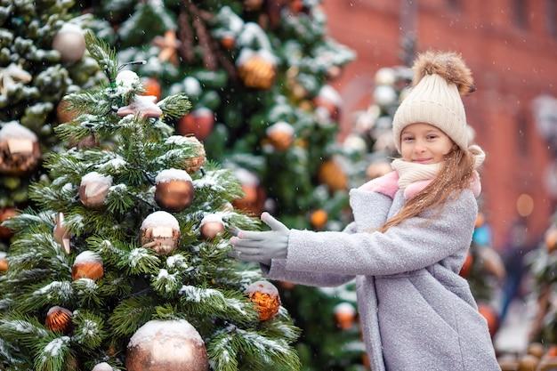 Weinig gelukkig meisje dichtbij sparrentak in sneeuw voor nieuw jaar.