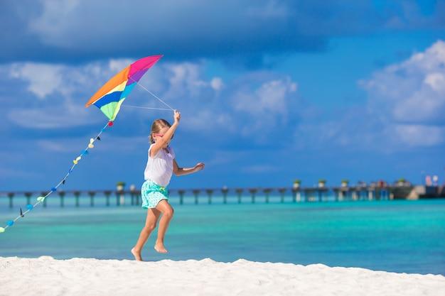 Weinig gelukkig meisje die met vliegende vlieger op tropisch strand spelen