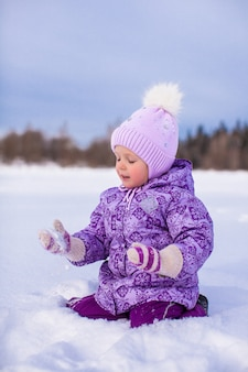 Weinig gelukkig meisje die pret op de sneeuw hebben bij de winter zonnige dag