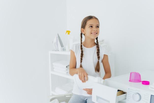 Weinig gelukkig meisje heeft twee vlechten vult wasmachine met vloeibaar wasmiddel