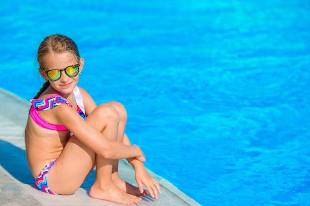 Weinig gelukkig meisje in openlucht zwembad geniet van haar vakantie