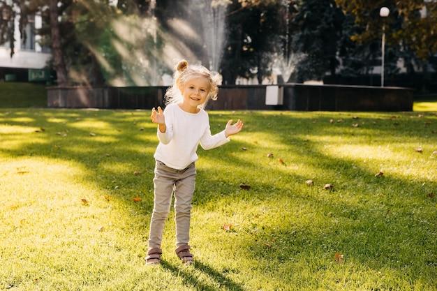 Weinig gelukkig meisje klappende handen buitenshuis