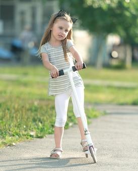 Weinig gelukkig meisje met een scooter