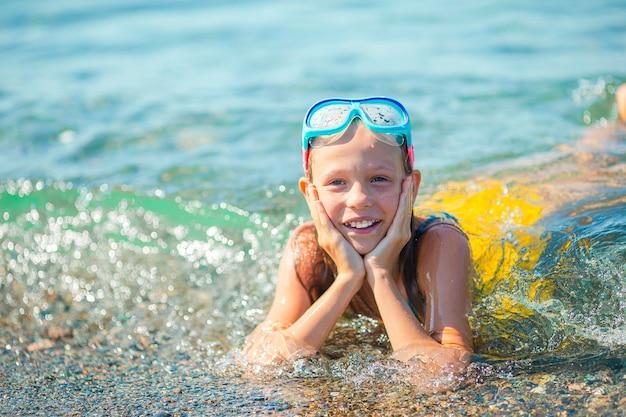 Weinig gelukkig meisje spetteren in helder turkoois water