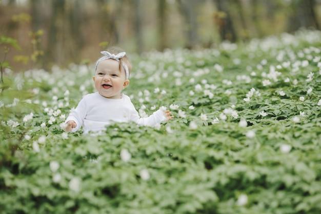 Weinig gelukkig meisje zit onder de bloemen in het bos