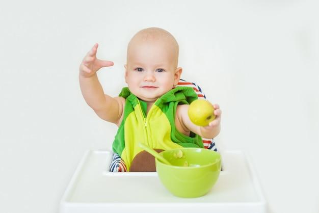 Weinig gelukkige baby met lepel zit op kinderstoel en eet pap op plaat