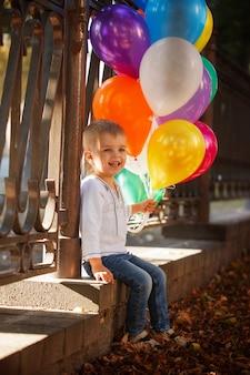 Weinig gelukkige jongen met kleurrijke ballonnen buiten in de zomer.
