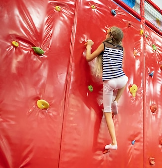 Weinig glimlachend blond meisje dat zich dichtbij rode klimmuur in de speelruimte bevindt