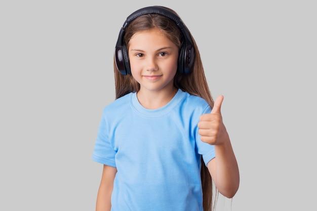 Weinig glimlachend meisje dat aan muziek luistert en duimen toont tegen een grijze achtergrond