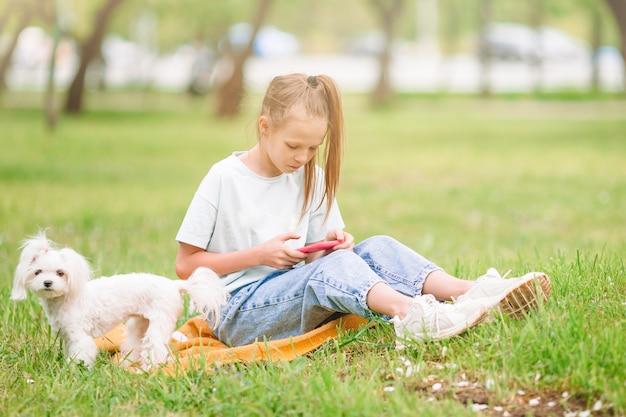 Weinig glimlachend meisje dat en puppy in het park speelt koestert